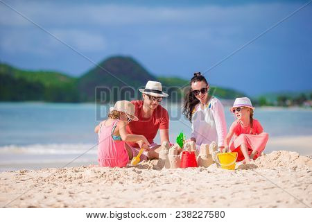 Family Making Sand Castle At Tropical Beach. Family Spend Time Together On Summer Vacation