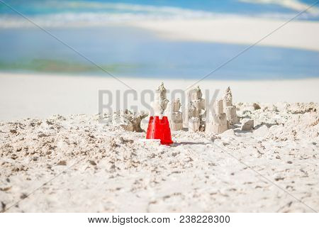 Sandcastle At White Tropical Beach With Plastic Kids Toys