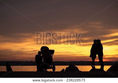 Young Family With A Baby In A Pushchair And Kids Silhouetted Against A Bright Colorful Orange Sunset