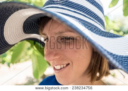 Close Up Of The Face Of A Woman In A Sunhat
