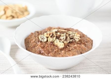 Chocolate Oatmeal Or Oat Porridge With Toasted Almond Slices And Grated Chocolate On Top Served In S