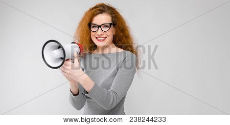 Portrait Of Cheerful Woman In Dress And Eyeglasses Isolated On Grey Background With Copyspace Speaki