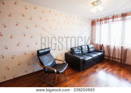 Empty Living Room Interior With Black Leather Chair And Sofa Near Bright Window