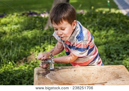 Cute Little Caucasian Boy Drinking Water From A Street Drinking Fountain. Thirst Stock Image.