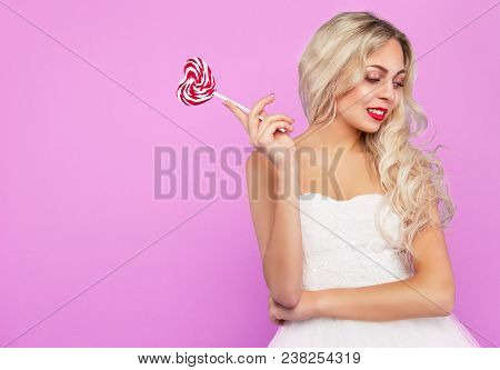 Pretty Blonde With A Lollipop. Thoughtful Blonde. Beautiful Blonde On Pink Background. Copy Space
