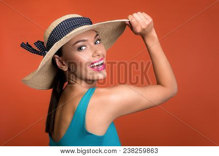 Summer Concept. Portrait Of Good Looking Woman Touching Hat On Her Head. She Is Looking At Camera An