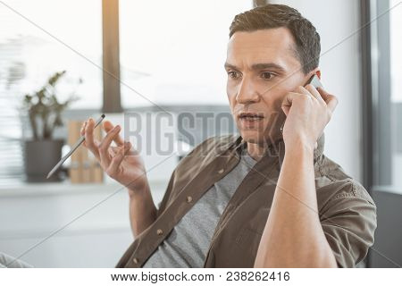 Portrait Of Surprised Young Employer Talking By Mobile While Holding Pencil In Hand. Serious Convers