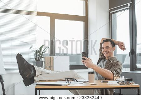 Full Length Portrait Of Happy Male Typing In Mobile While Resting At Table During Labor. Pleased Emp