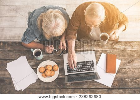 Calm Mature Husband And Wife Are Paying Taxes In Internet. They Are Sitting At Table In Kitchen And