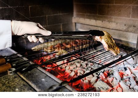 Chef Cooking Grilled Meat At A Restaurant. Barbecued Charred Steak And Shashlik