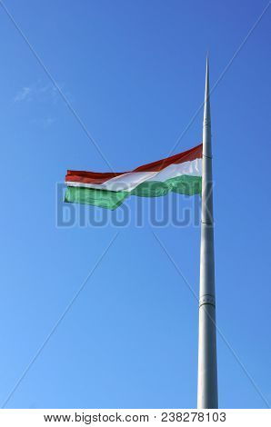 Hungarian National Flag On The Mast Against Blue Sky