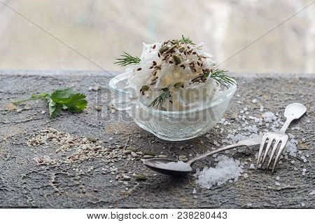 White Plate With Daikon Cutlery Large Salt And Seeds On A Concrete Background