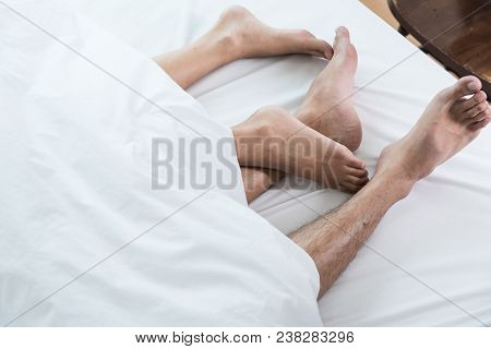 Close Up Of Feet Couple On Bed, Feet Of Couple In Comfortable Bed Under White Blanket