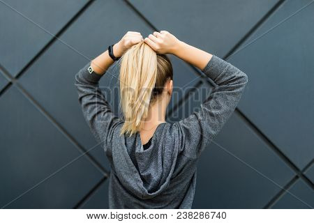 Sporty Fitness Woman Lacing Ponytail And Getting Ready For Urban Workout Or Running. Back View Of Fi