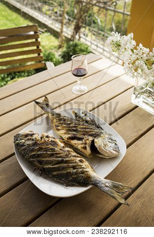 Grilled Gilt-head bream. Sea fish meal served outside poster