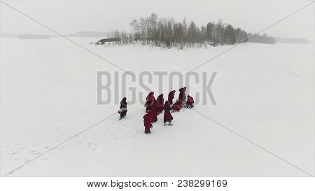 Meditating Monks In The Forest In Winter. Hooded People Follow Each Other In Snowy Woods Like Monks
