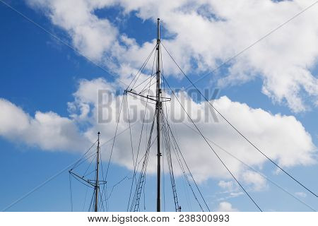 Masts Of A Sailing Ship On Blue Sky Background