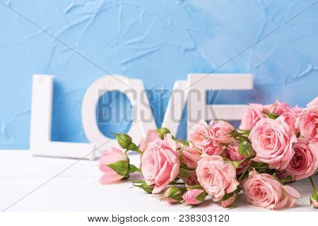 Pink Roses Flowers And  Word Love From Wooden Letters Against  Blue Textured  Wall. Floral Still Lif