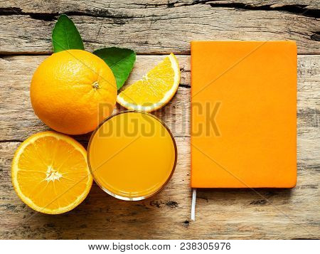 A Glass Of Fresh Orange Juice And Group Of Fresh Orange Fruits With Green Leaves, On Wooden Backgrou