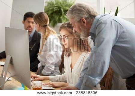 Aged Executive Manager Boss Checking Work Of Young Trainee Looking At Computer Screen In Office With