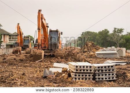 Heavy orange machine crawler loader or loader excavator, removing soil from ground  for site preparation at a civil construction site poster
