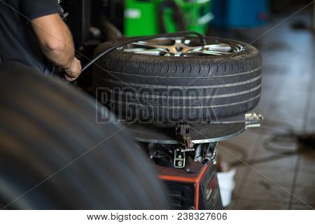 Tyre change - wheel balancing or repair and change car tire at auto service garage/ workshop by mechanic