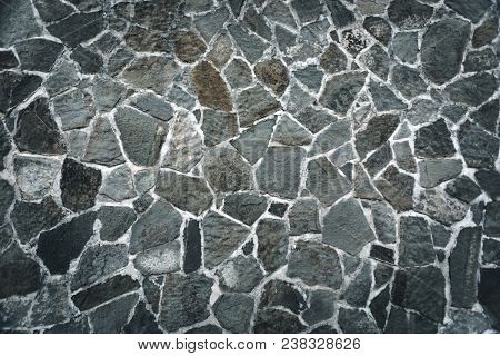 Stone wall background, gray brick fence, outdoors conctruction, building lined with decorative tiles, abstract textured wallpaper