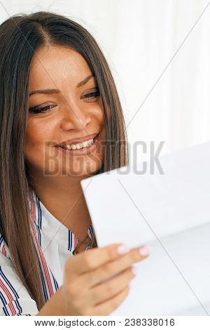 Woman Enjoying Good News In Writing. The Girl Reads A Letter With Good News Sitting On The Couch. An