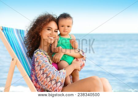 Young African American woman with daughter sitting on lounge chair at resort