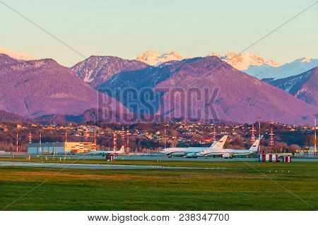 The Airdrome Of Sochi International Airport With Planes On The Background Of Mountains In Sunny Even