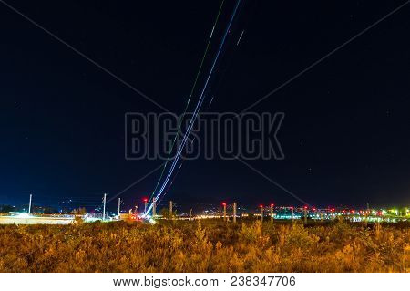 Light Trails Of Plane Taking Off On The Background Of Night Sky With Stars, Adler, Sochi, Russia