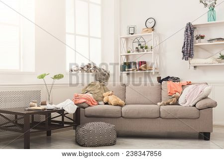 Sofa In Messy Living Room With Many Stack Of Clothes. Disorder And Mess At Home, Copy Space