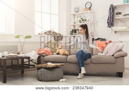 Desperate Helpless Woman Sitting On Sofa In Messy Living Room. Young Girl Surrounded By Many Stack O