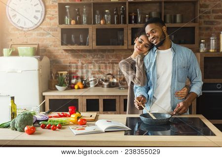 Happy African-american Couple Cooking And Tasting Healthy Food In Their Loft Kitchen At Home. Woman