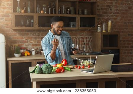 Happy African-american Man Watching Football On Laptop And Drinking Wine While Cooking Healthy Food