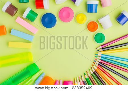 Flat Lay Lots Of Stationery On A Green Background, Multi-colored Paints, Pencils, Markers, Eraser, R