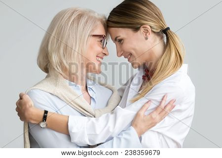 Attractive Aged Older Mother Hugging Adult Daughter Touching Foreheads, Happy Senior Lady Embracing