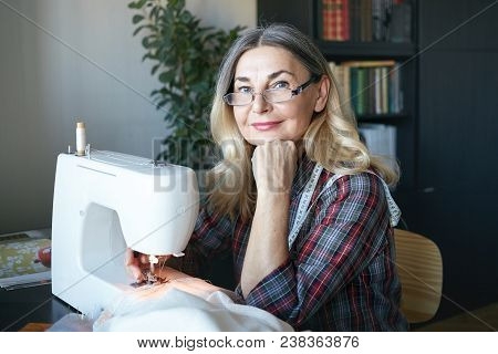 Cheerful Charming Mature Woman Dressmaker Creating New Fashionable Styles, Working On Sewing Machine
