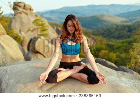Woman Meditating Outdoors On Top Of A Rock Copyspace. Long Haired Young Woman Meditating In The Moun