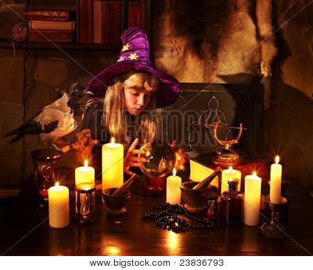 Witch  child with crystal ball. Halloween.