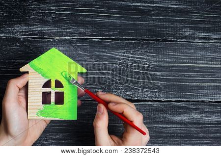 Man's Hand Paints The Wooden House In The Green Brush. Renovation And Renovation Of The House, Envir