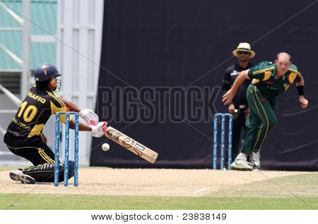 PUCHONG, MALAYSIA - SEPT 24: Guernsey's Jamie Nussbaumer watches Malaysia's Mohd Shafiq bat in this Pepsi ICC World Cricket League Div 6 finals on Sept 24, 2011 at the Kinrara Oval, Puchong, Malaysia.