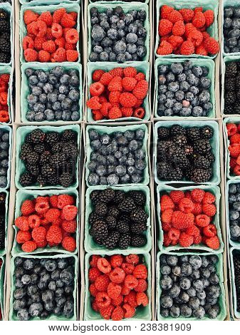Background Of Different Fruits And Berries. Sweet And Juicy Berry In Baskets. Blueberries, Raspberri