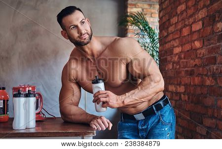 Portrait Of A Tall Stylish Shirtless Bodybuilder Dressed In Jeans, Prepares Protein Mixture Before M