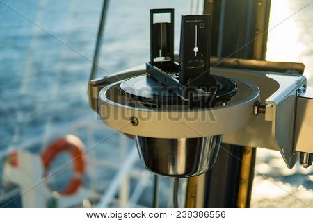 Close Up Of Nautical Marine Magnetic Compass On Yacht Or Boat With Beautiful Sunset On Background. C