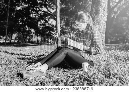 The Girl Sitting On A Green Grass With Cup Of Coffee And Reads The Book, Young Woman With Coffee Sit