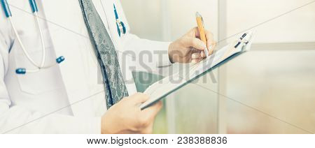 Close Up Of Hand Male Doctor Filling The Medical Form. Banner Panoramic Crop For Copy Space. Doctor