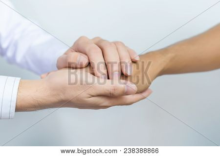Two People Holding Hands For Comfort. Doctor Consoling Relatives Of Patients In Hospital Concept. Do