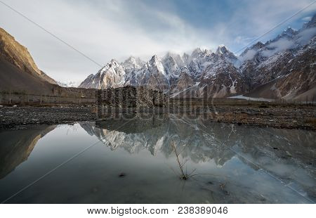 Mountain Landscape With Reflection On The Water. Stone Hut Stand Alone At Karakoram Range In Pakista