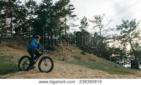 Fat Bike Also Called Fatbike Or Fat-tire Bike In Summer Driving Through The Hills. The Guy Is Riding